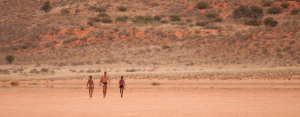 Two San Bushmen lead a tourist through the Kalahari.