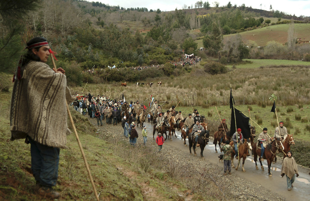 Members of the Mapuches Indians Movement ride their horses as a Chilean Mapuche stands guard during the burial ceremony of Jaime Facundo Mendoza Collio, who was killed during clashes with riot police, near Temuco city, some 680 km (422 miles) south of Santiago, August 16, 2009. Collio, 24, died on August 12, 2009 after being shot during clashes with police in a land dispute in southern Chile, local media reported. REUTERS/Jose Luis Saavedra (CHILE POLITICS CONFLICT)
