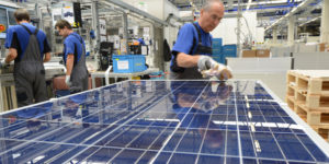 FREIBERG, GERMANY - AUGUST 14: A worker checks finished solar energy moduls at the Solarworld plant on August 14, 2013 in Freiberg, Germany. The troubled solar cells, modules and panels producer managed to recently avoid bankruptcy by reaching an agreement with its shareholders and other investors. Many solar energy equipment producers in Germany are facing difficult times due to stiff competition from China. (Photo by Matthias Rietschel/Getty Images)